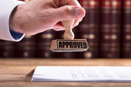 Primo piano della mano di un giudice che approva la forma di contratto in aula di tribunale Archivio Fotografico - 99571867