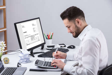 Young Businessman Calculating Invoice With Calculator At Desk Stok Fotoğraf