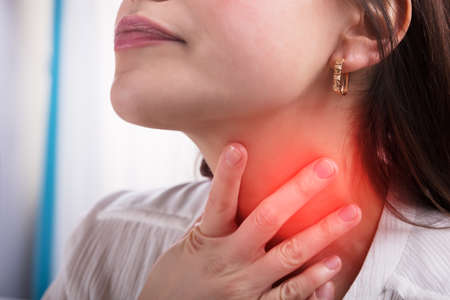 Close-up Of A Woman's Hand Touching Her Sore Throat