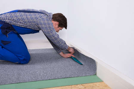Side View Of A Male Worker Fitting Grey Carpet On Floor Archivio Fotografico