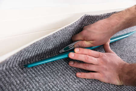 Carpet Fitter's Hand Fitter Carpet With Cutter Stockfoto - 99572068