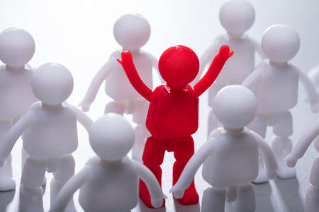 Red Human Figure Surrounded By Team Representing Unity