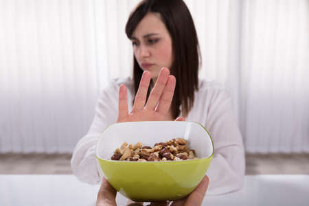 Woman Refusing Bowl Of Nut Food Offered By A Person