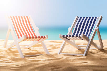 Close-up Of Two Blue And Red Striped Deck Chairs On Sandy Beach