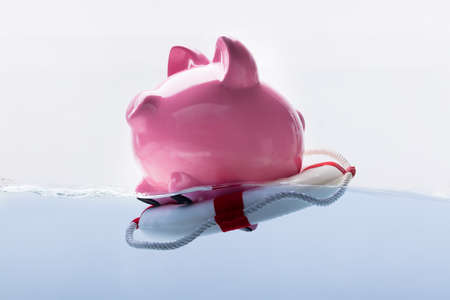 Close-up Of A Pink Piggy Bank Floating On Lifebuoy Imagens - 99828078