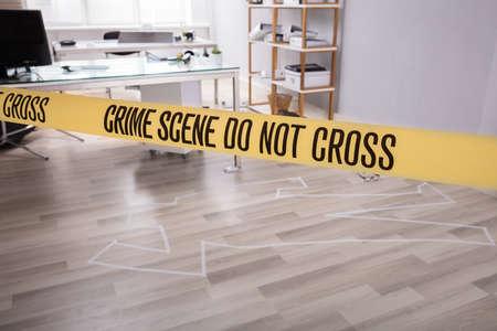 Gele misdaadscène tape in de buurt van krijt contouren van vermoord slachtoffer