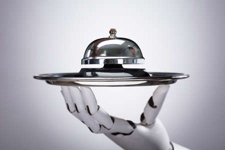 Robotic Hand Holding Service Bell In Plate Against Grey Background Banque d'images - 99828218