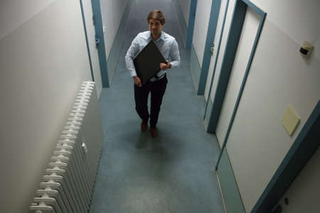 Young Man Stealing Computer Monitor Walking In Building Corridor Фото со стока