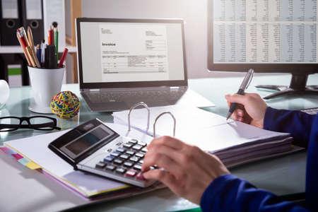 Nahaufnahme der Hand eines Wirtschaftlers, die Rechnung am Arbeitsplatz berechnet