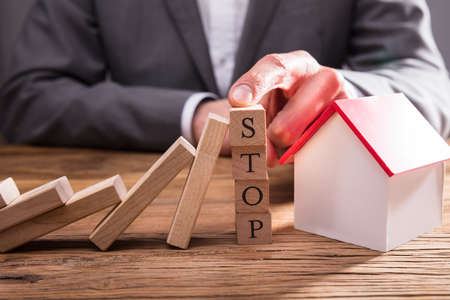 Businessperson Stopping Wooden Dominos From Falling By Placing Finger On Wooden Blocks