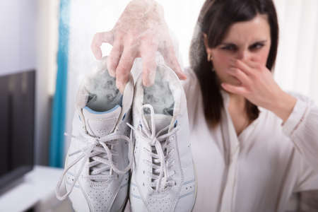 Woman Holding Her Smelling Exercise Shoe With Steam Coming Out From It Stock Photo