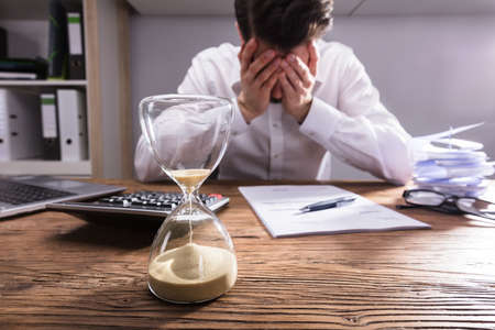 Close-up Of A Hourglass In Front Of Upset Businessman In Office