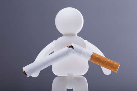 Human Figure With Broken Cigarette On Grey Background Stock Photo