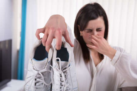 Woman Holding Dirty Stinky Shoes Covering Her Nose Imagens