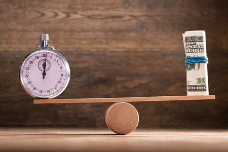 Close-up Of Stopwatch And Rolled Up Banknotes On Seesaw Against Wooden Background