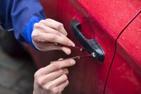 Close-up Of Persons Hand Opening Red Car Door With Lockpicker