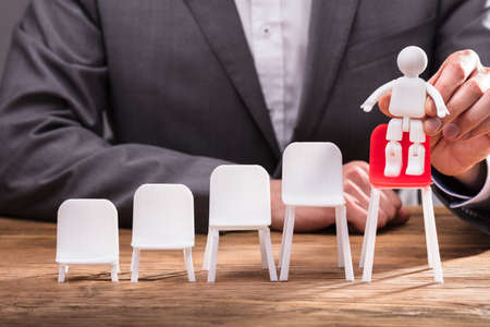 Close-up Of A Businesspersons Hand Placing Human Figure On Red Chair Over Wooden Desk Stock Photo