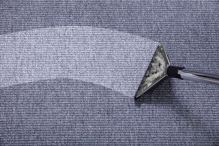 Nahaufnahme eines Staubsaugers über grauem Teppich