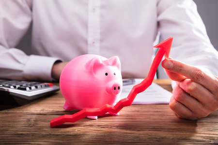 Human Hand Holding Red Arrow In Front Of Pink Piggybank On Wooden Desk