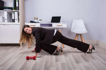 Photo Of Businesswoman Doing Pushups On Hardwood Floor Stockfoto