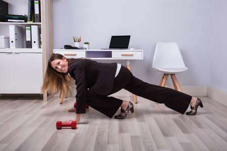 Foto der Geschäftsfrau, die Liegestütze auf Hartholzboden tut Standard-Bild