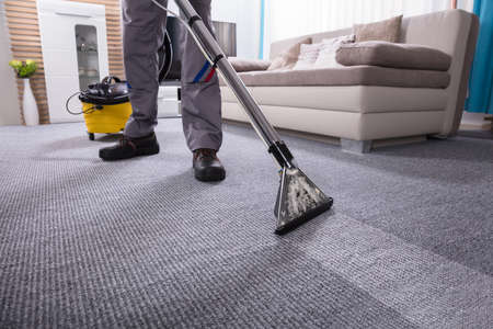 Lage sectie van een persoon die het tapijt met een stofzuiger in de woonkamer schoonmaakt