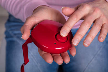 Close-up Of Womans Hand Pressing Personal Alarm Button