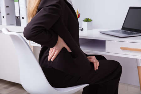 Mature Businesswoman Suffering From Back Pain At Workplace
