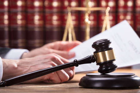 Close-up Of A Gavel In Front Of Human Hand Holding Document In Courtroom