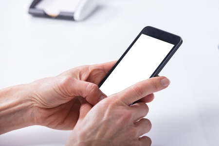 Human Hand Using Mobile Phone With Blank White Screen