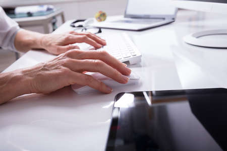 Close-up Of A Businesspersons Hand Typing On Computer Keyboard