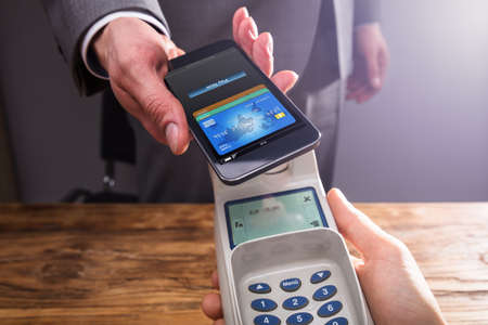 Close-up Of A Businesspersons Hand Paying With Smartphone Using NFC Technology Over Wooden Desk