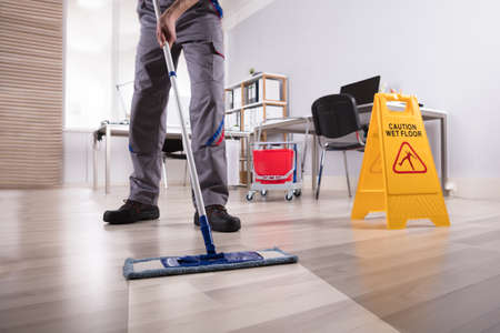 Low Section Of Male Janitor Cleaning Floor With Caution Wet Floor Sign In Office Фото со стока