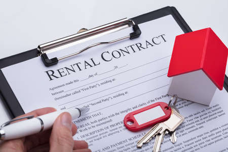 Close-up Of Key Over A Persons Hand Filling Rental Contract Form