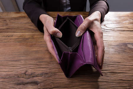 Close-up Of A Businesspersons Hand Holding Empty Purse Over Wooden Desk