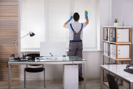 Rear View Of A Male Worker Cleaning Window Blinds With Sponge In Office