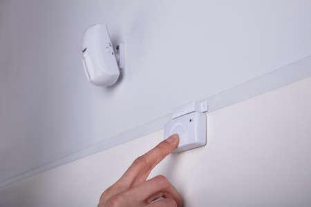 Close-up Of A Persons Finger Pressing Security System Door Sensor