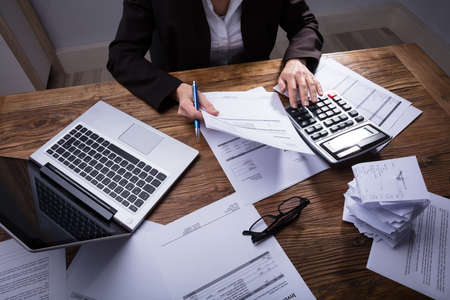 Businessperson Calculating Invoice With Calculator In Office