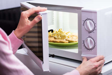 Photo Of Woman's Hands Opening Microwave Oven Door