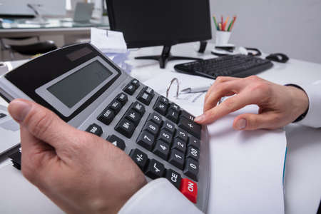 Close-up Of A Businesspersons Hand Using Calculator In Office