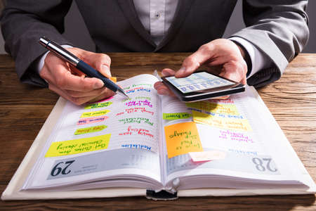 Businesspersons Hand Writing Schedule In Diary With Pen On Wooden Desk