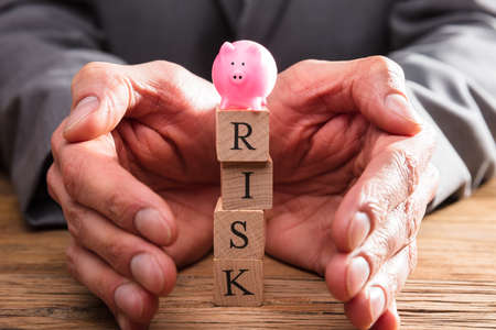 Businessperson Hand Protecting Pink Piggybank Over Wooden Blocks With Risk Word