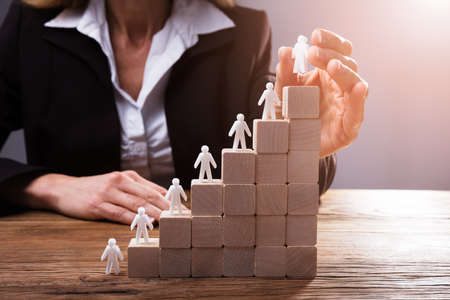 Businesspersons Hand Placing Human Figures On Staircase Made Up Of Wooden Blocks