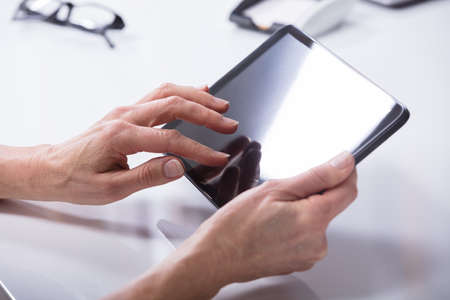 A Persons Hand Holding Digital Tablet With Blank Screen