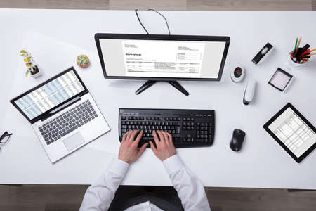 Young Businessman Using Laptop With Computer Screen Showing Invoice