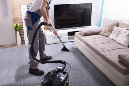 Close-up Of A Male Janitor Using Vacuum Cleaner For Cleaning The Carpet In Living Room Фото со стока