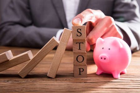 Persons Finger On Stop Wooden Blocks Stopping Dominos From Falling Over Piggybank Фото со стока