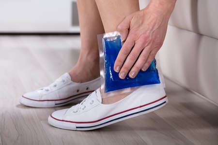 Close-up Of Womans Hand Holding Cool Gel Pack On Her Ankle