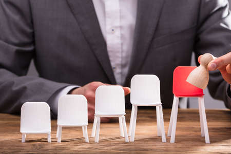 Close-up Of Businesspersons Finger Placing Pawn On Red Chair Over Wooden Desk