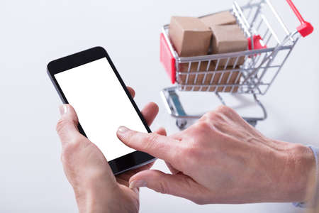 A Person Hand Showing Mobile Phone With Blank Screen And Shopping Cart On The Background Фото со стока